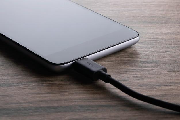 木製の机の白い背景で充電モバイルスマートフォン