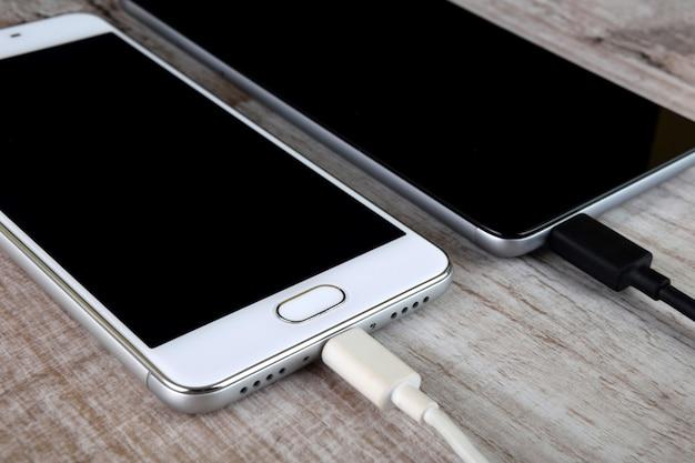 木製の机で充電するモバイルスマートフォン