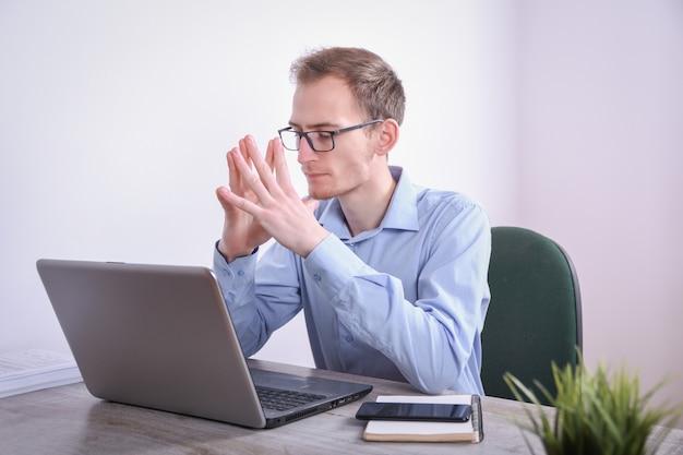 Портрет молодого бизнесмена сидя на его технологии настольного компьютера настольного компьютера в офисе. интернет-маркетинг, финансы, концепция дела
