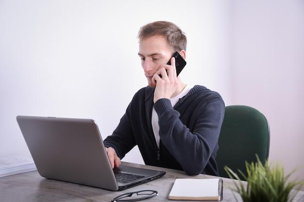 オフィスで彼の机のデスクトップノートパソコン技術に座っている若いビジネスマンの肖像画。インターネットマーケティング、金融、ビジネスコンセプト