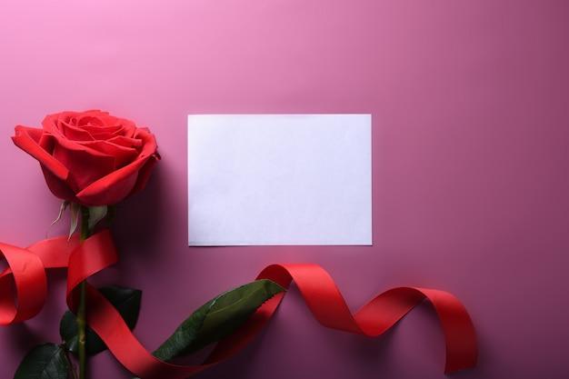 バレンタインデーの背景グリーティングカード愛のシンボル、ピンクの背景にバラで赤い装飾。コピースペースとテキストの平面図。