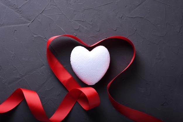 バレンタインデーの背景グリーティングカードは、石の背景に心でシンボル、赤い装飾が大好きです。コピースペースとテキストの平面図。