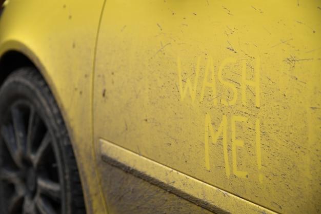 Напишите слова с надписью «помой меня» на очень грязной поверхности автомобиля. концепт автомойки.