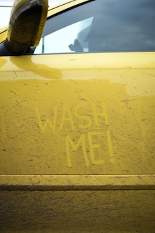 車の非常に汚れた表面に碑文のテキスト「ウォッシュミー」を書きます。コンセプトカーウォッシュ。