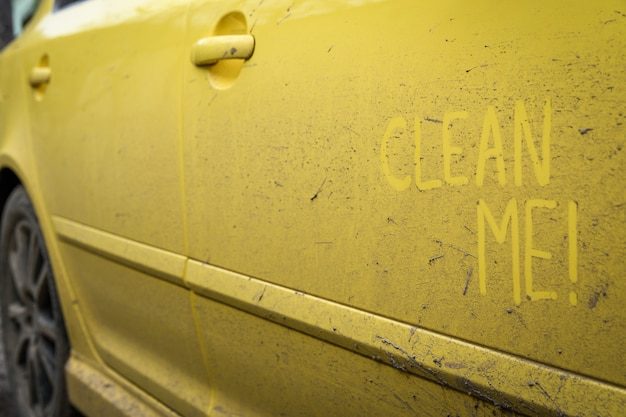 Напишите слова с надписью «очистите меня» на очень грязной поверхности автомобиля. концепт автомойки.