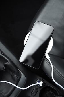 携帯電話、スマートフォンの充電バッテリー、車のプラグのワイヤレス充電をクローズアップ