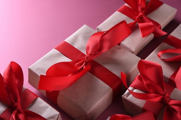 バレンタインデーの背景グリーティングカードは、ピンクの背景のギフトボックスにシンボル、赤い装飾が大好きです。コピースペースとテキストの平面図。