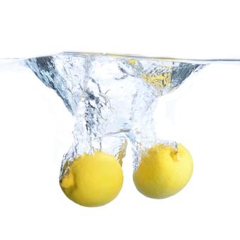Лимоны в воде с пузырьками и брызгами. крупный план. изолированный на белизне. концепция и идея с лимонами