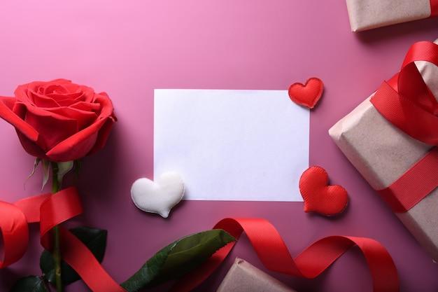 バレンタインデーの背景グリーティングカード愛のシンボル、ピンクの背景にメガネハートバラギフトと赤い装飾。コピースペースとテキストの平面図。