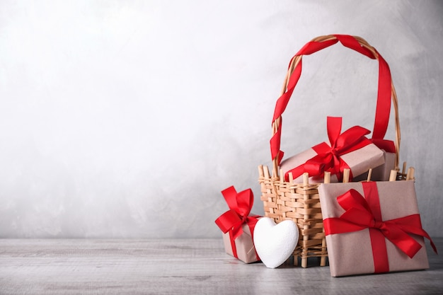 グリーティングカードバレンタインの心と木製の背景にバスケットのギフト。テキストグリーティング用のスペース
