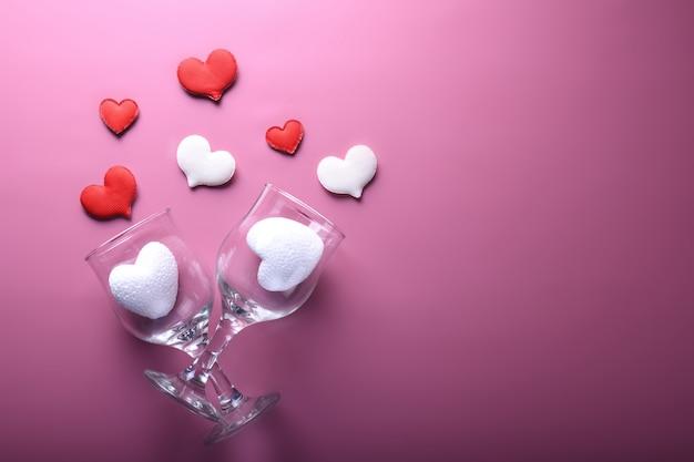 バレンタインデーの背景グリーティングカード愛のシンボル、ピンクの背景に眼鏡の赤い装飾。コピースペースとテキストの平面図。