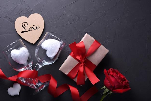 Символы влюбленности поздравительной открытки предпосылки дня валентинки, красное украшение с подарками роз сердца стекел на каменной предпосылке. вид сверху с копией пространства и текста. плоская планировка