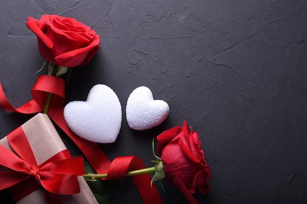 バレンタインデーの背景グリーティングカード愛のシンボル、石の背景にメガネハートバラギフトと赤い装飾。コピースペースとテキストの平面図。