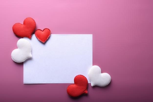 バレンタインデーの背景グリーティングカードは、ピンクの背景に心でシンボル、赤い装飾が大好きです。コピースペースとテキストの平面図。