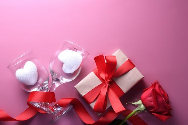 Символы влюбленности поздравительной открытки предпосылки дня валентинки, красное украшение с подарками роз сердца стекел. вид сверху с копией пространства и текста. плоская планировка