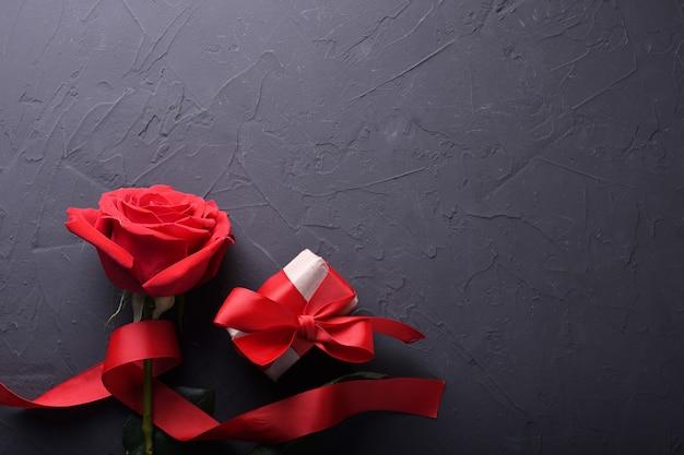 Символы влюбленности поздравительной открытки предпосылки дня валентинки, красное украшение с розами на каменной таблице. вид сверху с копией пространства и текста. плоская планировка