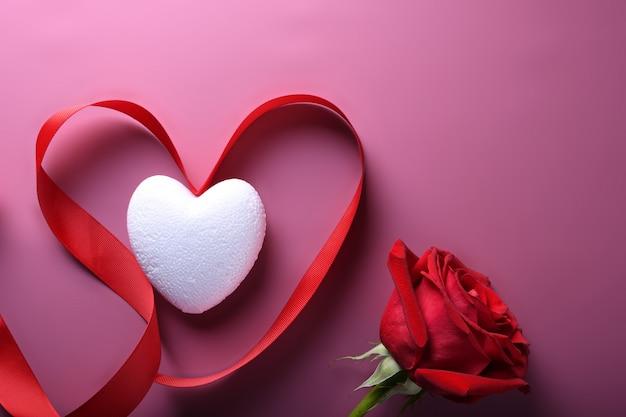 Символы влюбленности поздравительной открытки предпосылки дня валентинки, красное украшение с сердцем. вид сверху с копией пространства и текста. плоская планировка