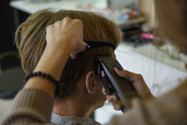 Парикмахерские услуги. мужчина стрижет волосы у парикмахера-стилиста в парикмахерской. ножницы расческа, машинка для стрижки крупным планом. парикмахер за работой. крупным планом стричь волосы.