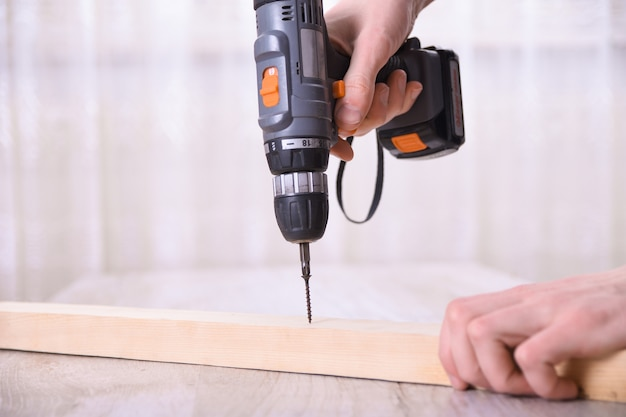 男は新しい家のインストールで電動ドライバーを使用して家具アセンブリで作業しています-ハンドツールのコンセプトを使用して技術者の現場作業