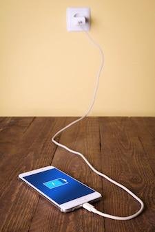 モバイルスマートフォン、木製の机で充電する電話