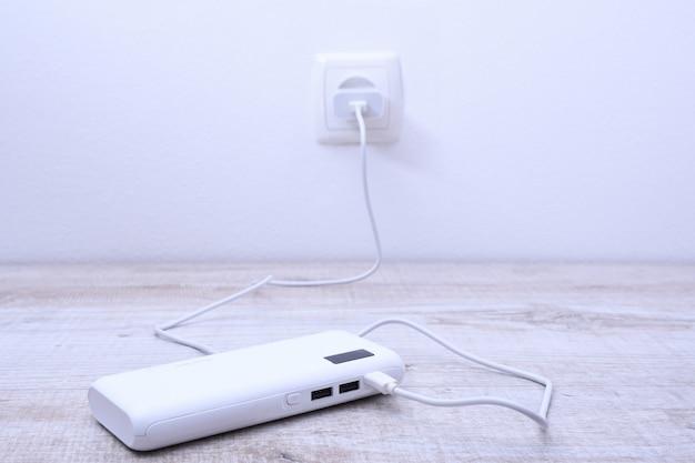 充電のために壁のソケットに差し込まれた黒い電話の電源銀行