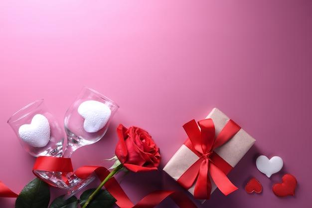 Символы влюбленности поздравительной открытки предпосылки дня валентинки, красное украшение с подарками роз сердца стекел. вид сверху