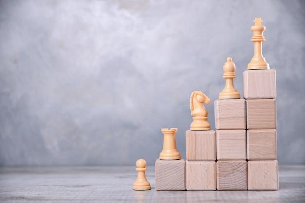 Деревянные кубики сложены в виде лестниц на деревянном столе. концепция развития, роста, босс, лучший. с шахматными фигурами