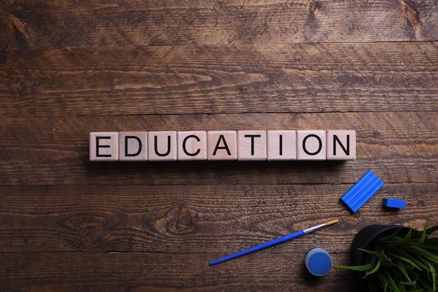 Слово образования деревянные кубики, блоки на тему образования, развития и обучения на деревянном столе. вид сверху. место для текста.