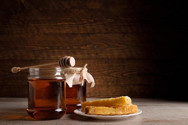 Мёд в банках и соты на деревянной ложке по дереву