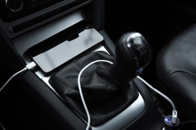携帯電話、スマートフォン充電バッテリー、車のプラグで充電をクローズアップ