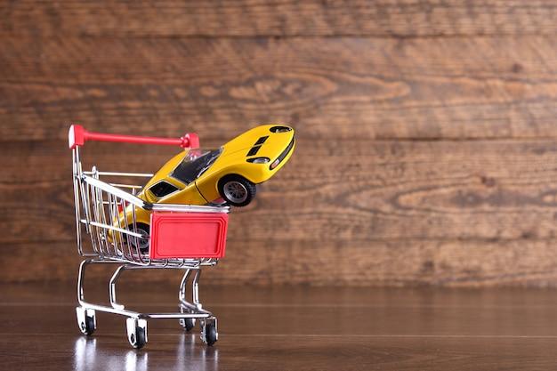 新しい車を購入する概念。木製のテーブルに買い物かごのおもちゃの車