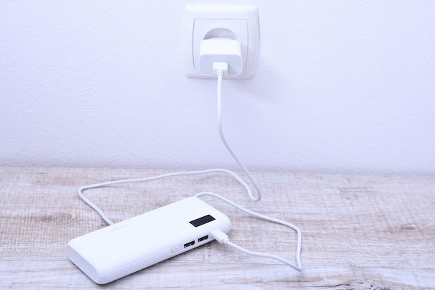 木製のテーブルで充電するための壁のソケットに差し込まれている白い電話の電源銀行