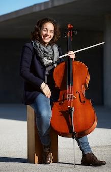 彼女の楽器に満足して笑っている若い女性