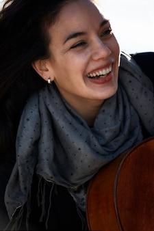 Молодая брюнетка женщина смеется с шарфом на шее