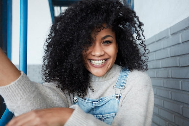 Молодая негритянка с афро волосами смеется и наслаждается