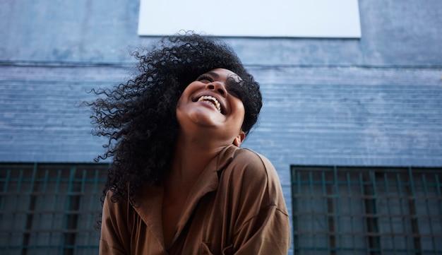 笑いと楽しんでアフロ髪の若い黒人女性