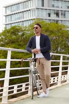 彼の自転車の横に立っている人