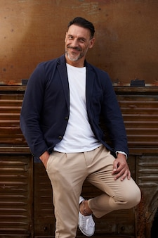 さびた色付きの背景に笑みを浮かべて身に着けている中年の男