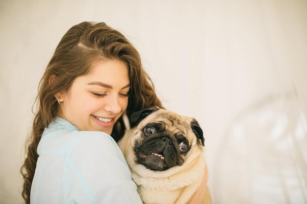 Женщина обнимает животное мопс. прекрасный семейный портрет