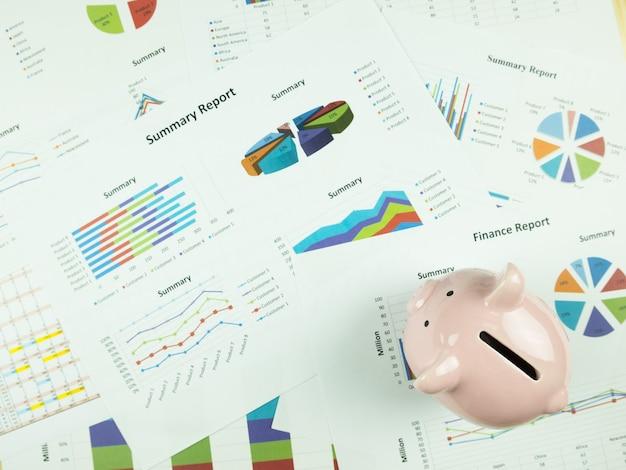 テーブルの上のピンクの貯金箱と事業報告チャートと財務グラフ分析。