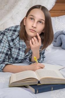Студентка колледжа лежит в постели, проводит свободное время в спальне.
