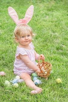 Прелестная белокурая девушка малыша нося уши зайчика играя с пасхальными яйцами в корзине сидя в солнечном саде