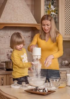 Мама и ее маленький ребенок готовят на кухне.