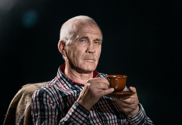 Крупным планом портрет пожилого сурового человека.