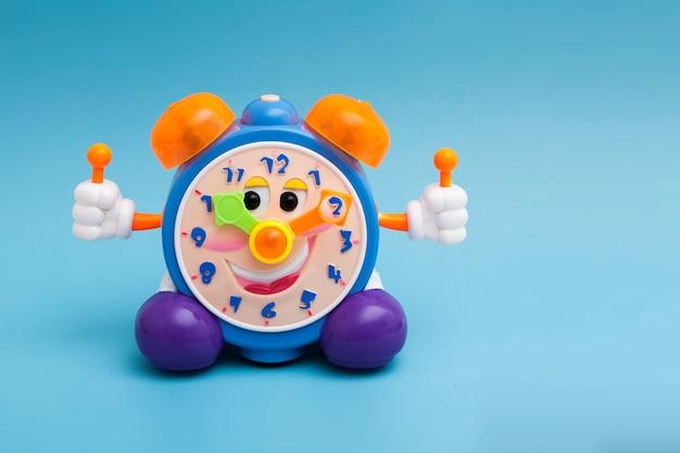 Забавный цветной будильник на синем фоне. детский игрушечный будильник с глазами и улыбкой.