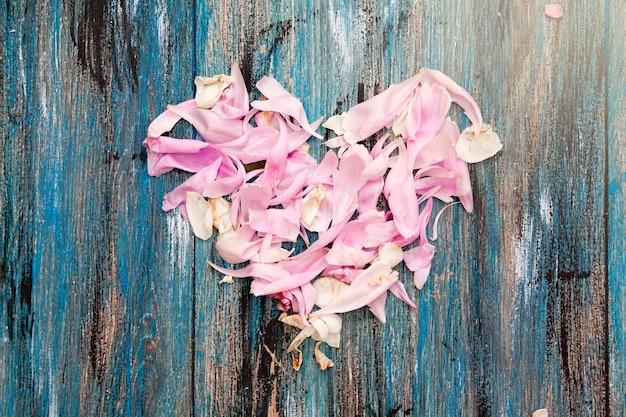 木製のテーブルにピンクと白の花びらの中心。バレンタインの日や結婚式のコンセプト