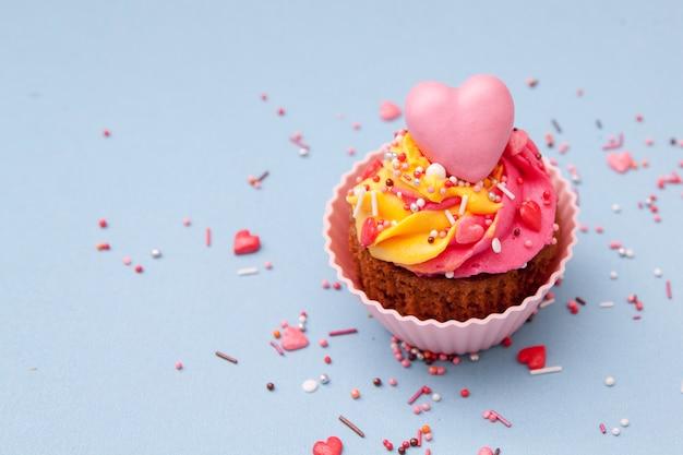 クリームとハートのカップケーキ-バレンタインデーの休日のペストリー。青い表面。 。