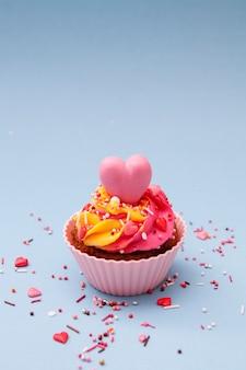 クリームとハートのカップケーキ-バレンタインデーの休日のベーキング。青色の背景。