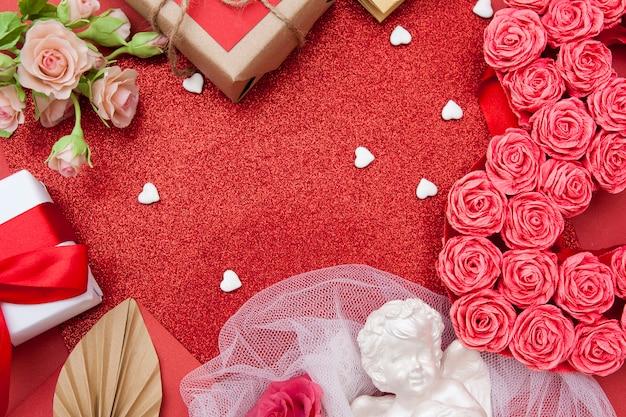 花とギフトの平面図。 。バレンタインデーの赤いキラキラ背景