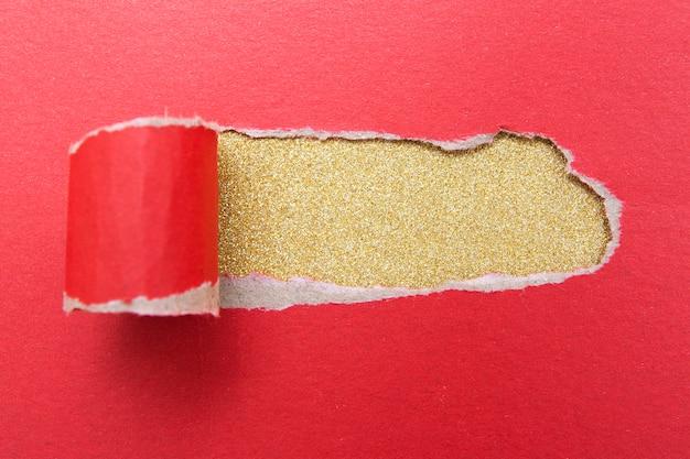 ゴールドラメの表面に赤い紙のシートの穴